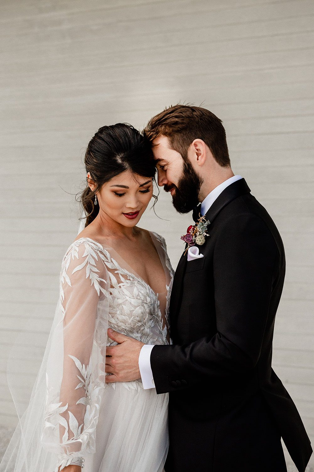 Bride wearing bespoke designer wedding dress by Vinka Bridal Boutique NZ, adorned with delicate applique lace and puffed sleeves - embrace at wall