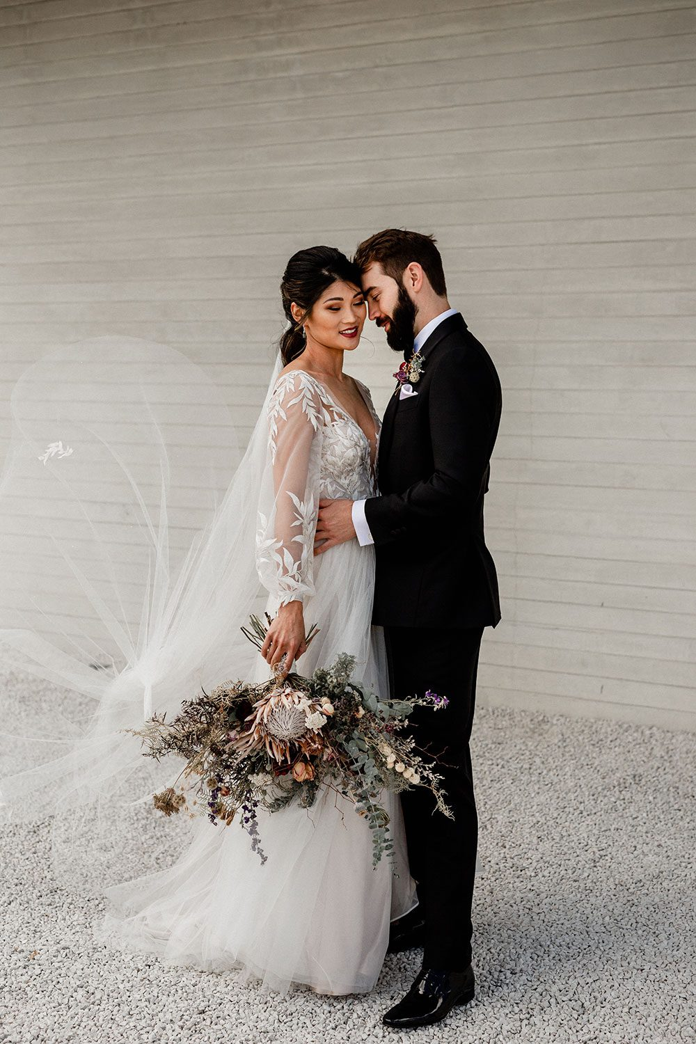 Bride wearing bespoke designer wedding dress by Vinka Bridal Boutique NZ, adorned with delicate applique lace and puffed sleeves - embrace at wall with groom
