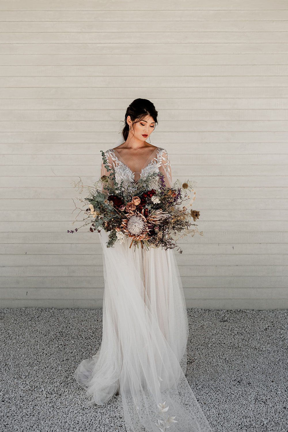 Bride wearing bespoke designer wedding dress by Vinka Bridal Boutique NZ, adorned with delicate applique lace and puffed sleeves - holding bouquet