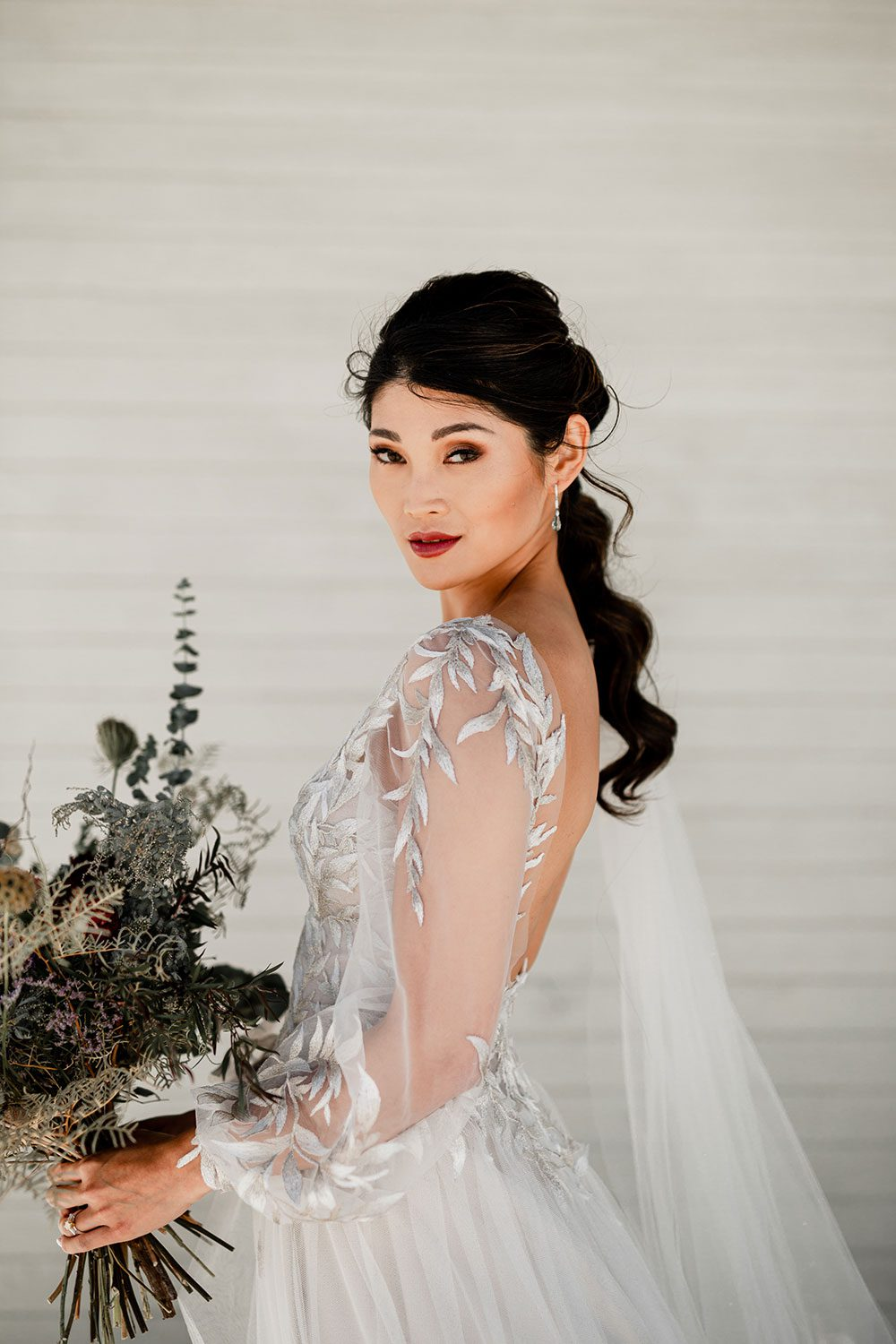 Bride wearing bespoke designer wedding dress by Vinka Bridal Boutique NZ, adorned with delicate applique lace and puffed sleeves - side holding bouquet