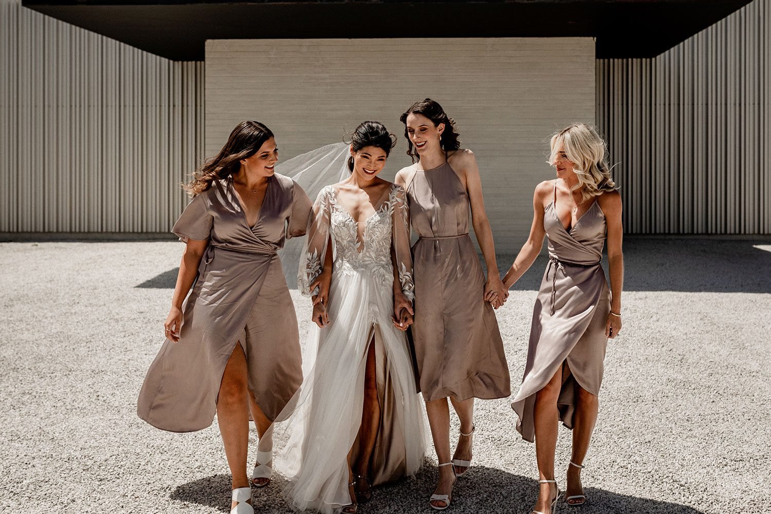 Bride wearing bespoke designer wedding dress by Vinka Bridal Boutique NZ, adorned with delicate applique lace and puffed sleeves - walking with bridesmaids