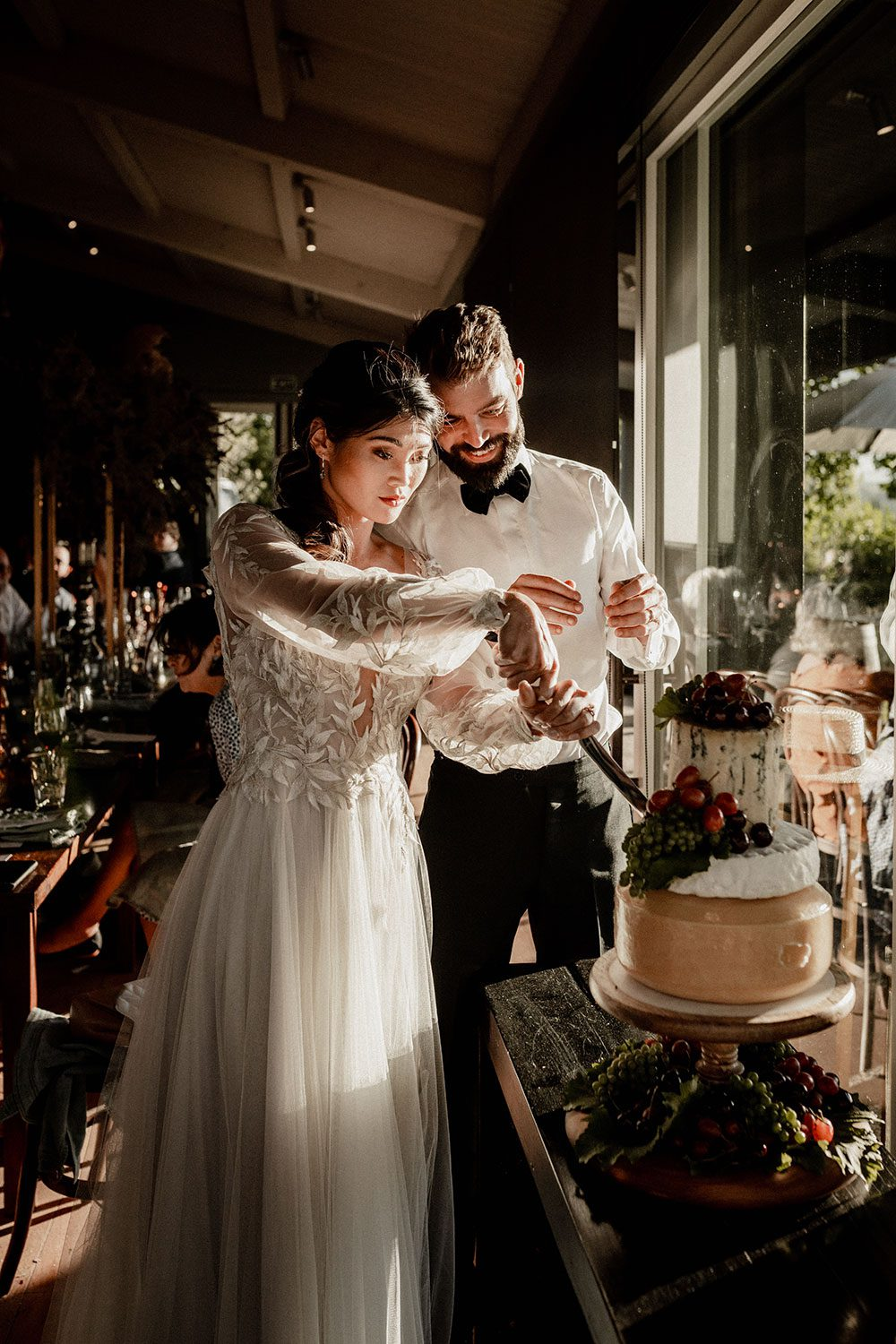 Bride wearing bespoke designer wedding dress by Vinka Bridal Boutique NZ, adorned with delicate applique lace and puffed sleeves - cutting cake