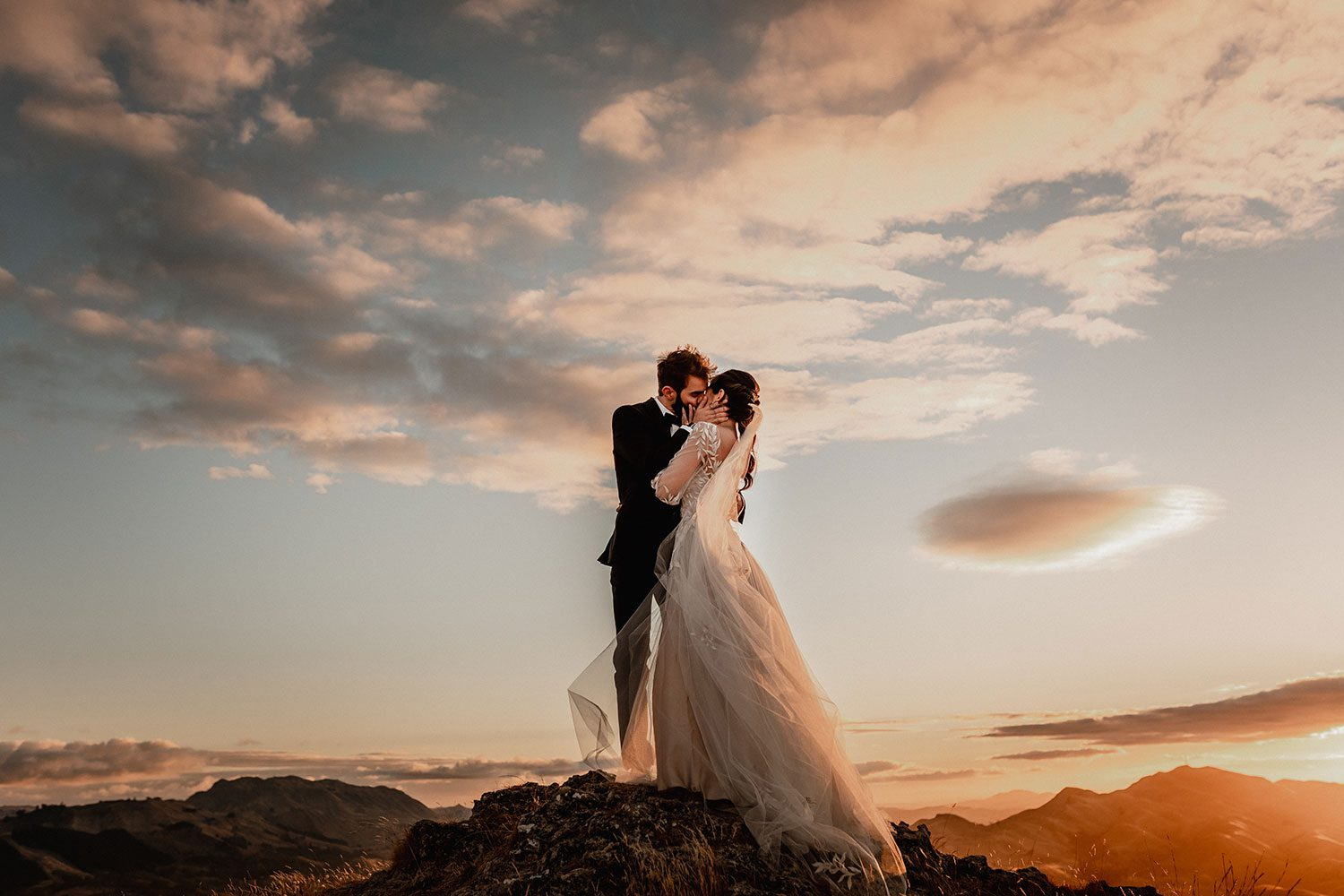 Bride wearing bespoke designer wedding dress by Vinka Bridal Boutique NZ, adorned with delicate applique lace and puffed sleeves - embrace on hill