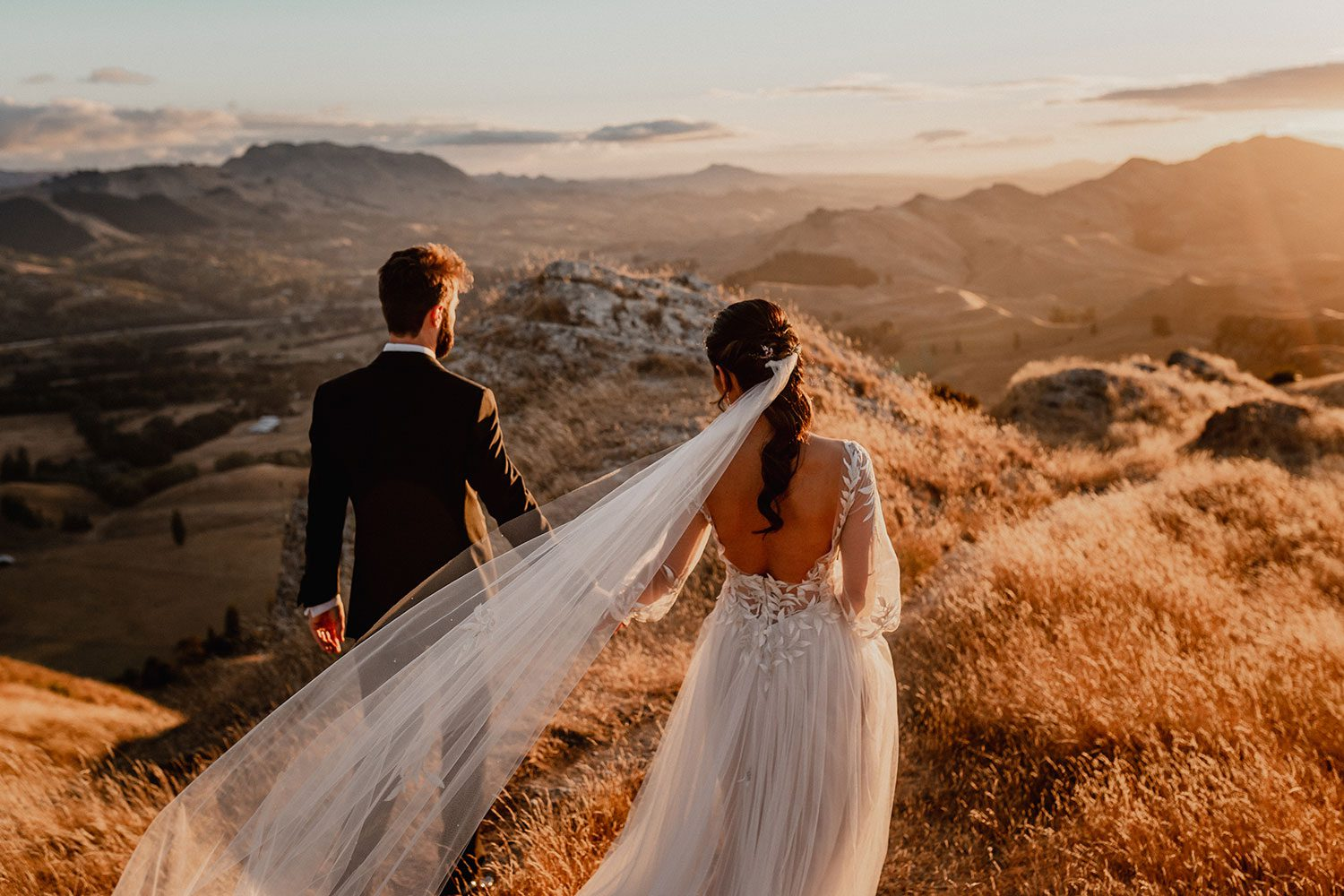 Bride wearing bespoke designer wedding dress by Vinka Bridal Boutique NZ, adorned with delicate applique lace and puffed sleeves - holding hands on hill