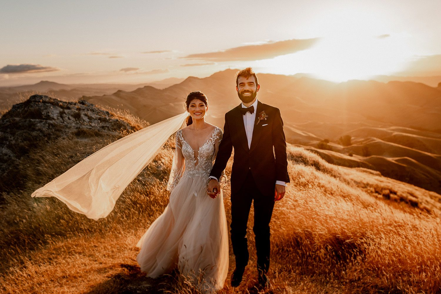 Bride wearing bespoke designer wedding dress by Vinka Bridal Boutique NZ, adorned with delicate applique lace and puffed sleeves - sunset holding hands