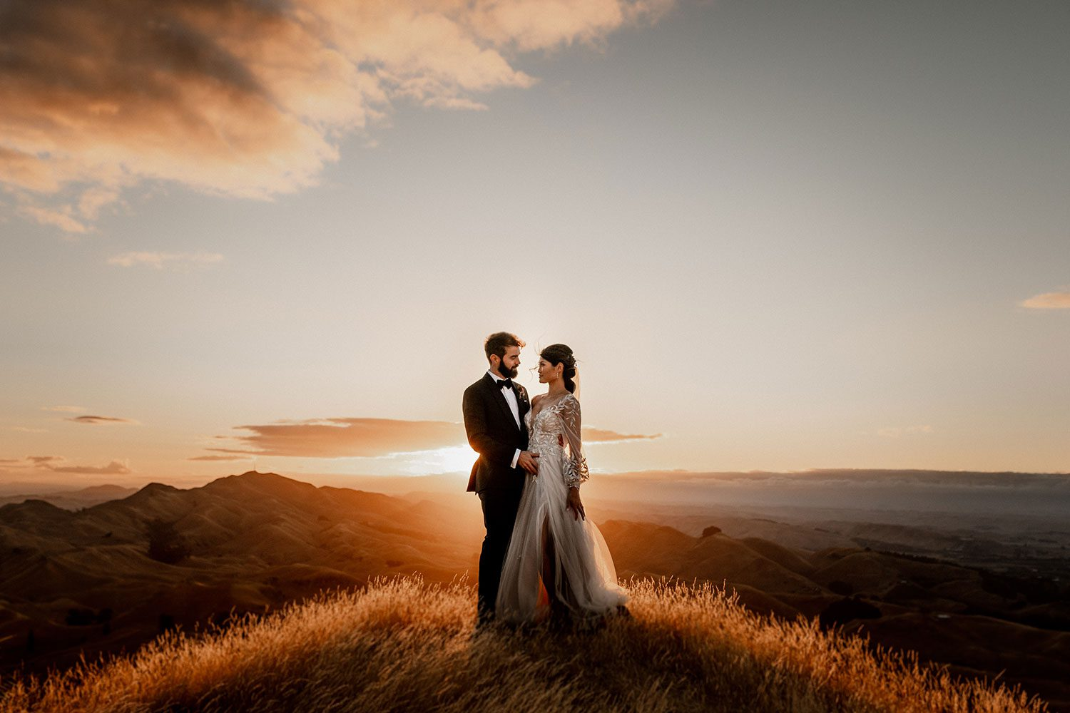 Bride wearing bespoke designer wedding dress by Vinka Bridal Boutique NZ, adorned with delicate applique lace and puffed sleeves - profile on hill