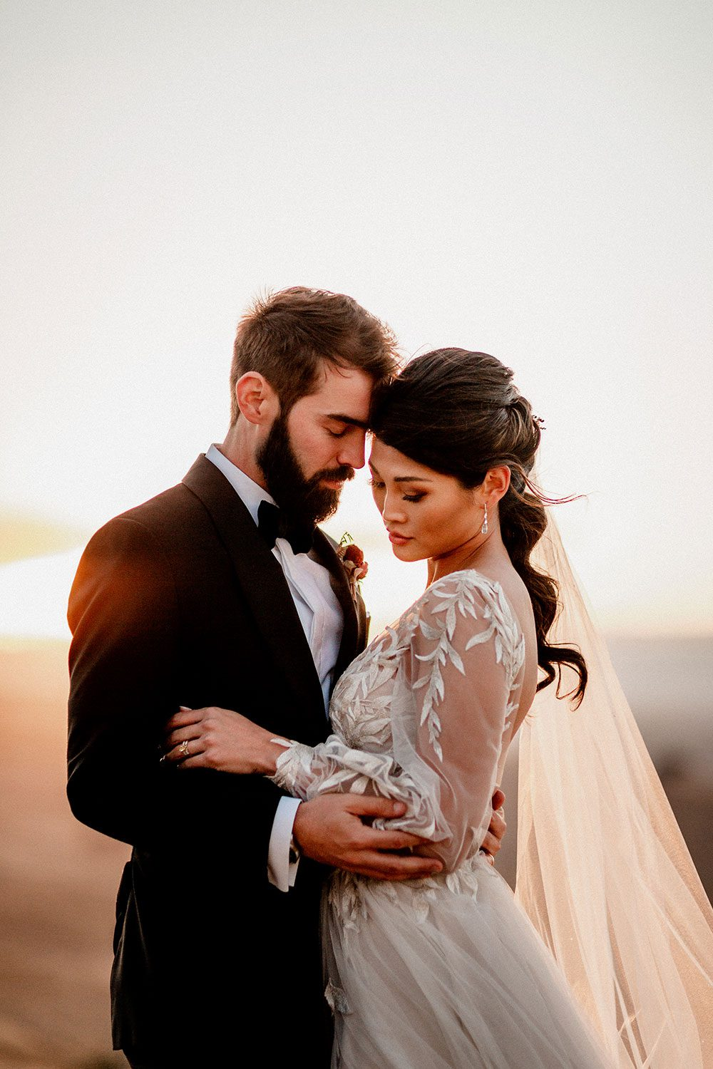 Bride wearing bespoke designer wedding dress by Vinka Bridal Boutique NZ, adorned with delicate applique lace and puffed sleeves- close profile