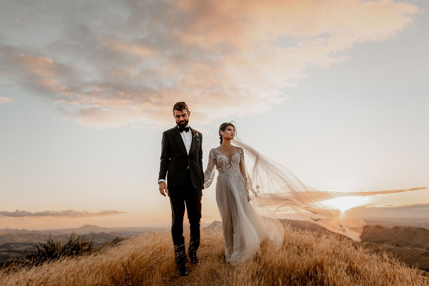 Bride wearing bespoke designer wedding dress by Vinka Bridal Boutique NZ, adorned with delicate applique lace and puffed sleeves - walking on hill