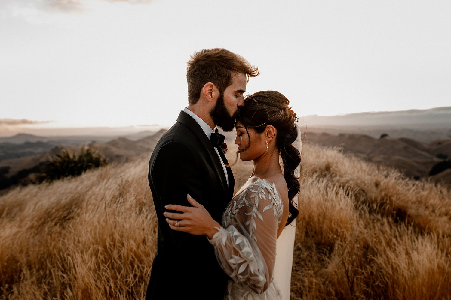 Bride wearing bespoke designer wedding dress by Vinka Bridal Boutique NZ, adorned with delicate applique lace and puffed sleeves - profile kiss