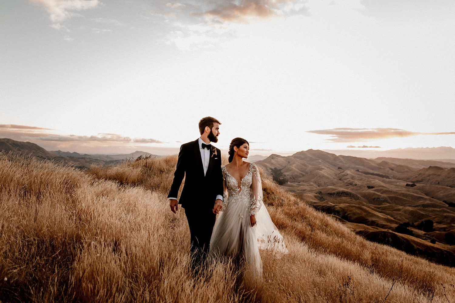 Bride wearing bespoke designer wedding dress by Vinka Bridal Boutique NZ, adorned with delicate applique lace and puffed sleeves - on hill looking away