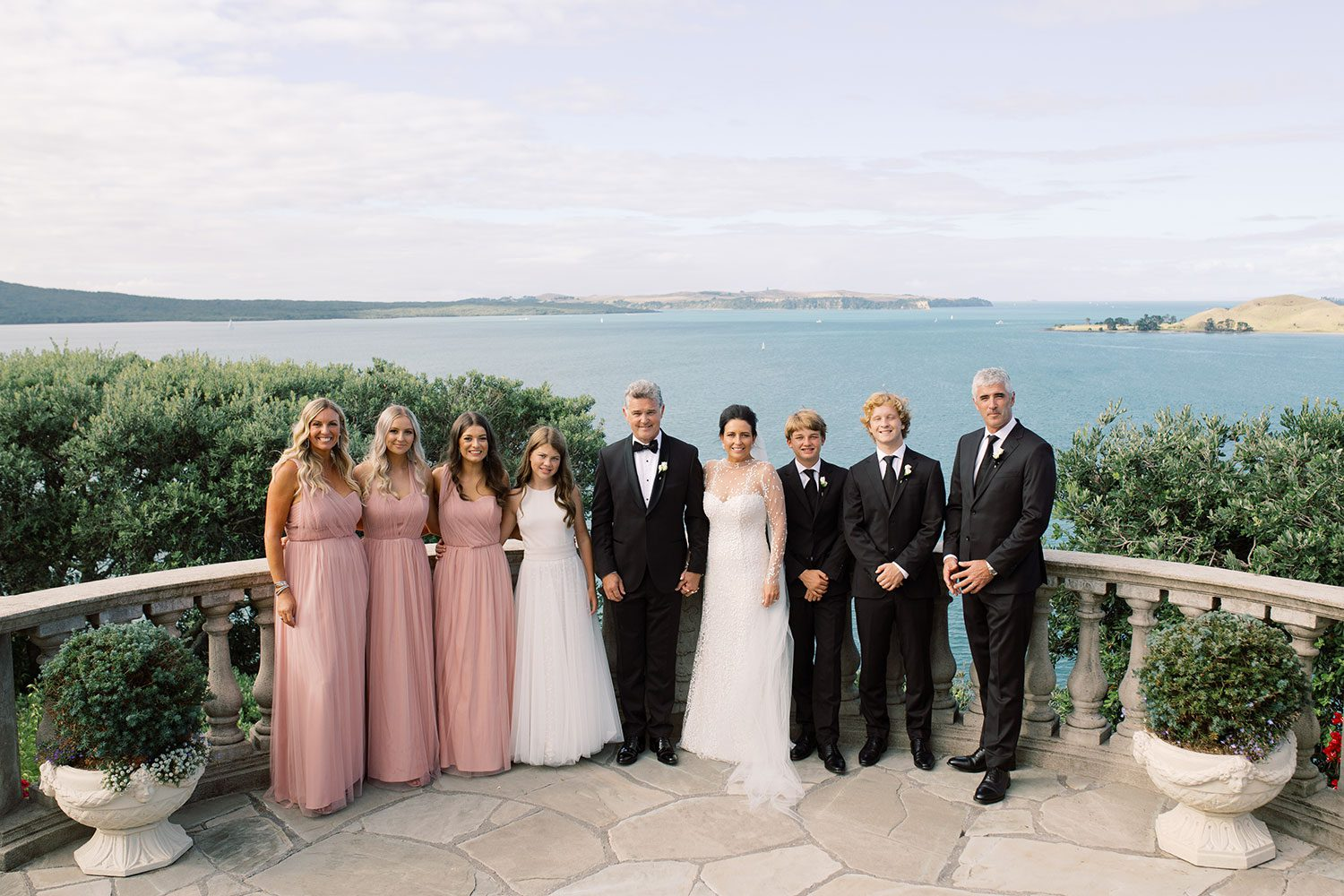 Bride wearing bespoke gown by Auckland wedding dress designer Vinka Design, with a high neckline and delicate spotted embroidery - bridal party