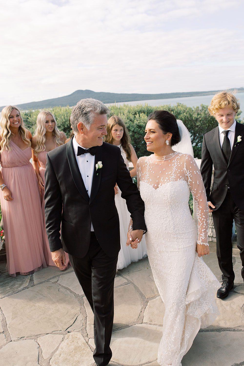 Bride wearing bespoke gown by Auckland wedding dress designer Vinka Design, with a high neckline and delicate spotted embroidery - with groom holding hands