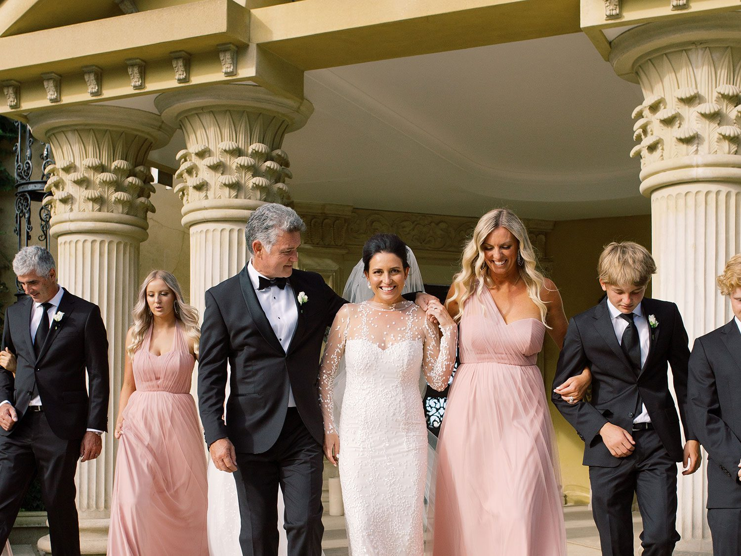 Bride wearing bespoke gown by Auckland wedding dress designer Vinka Design, with a high neckline and delicate spotted embroidery - with groom and bridal party walking