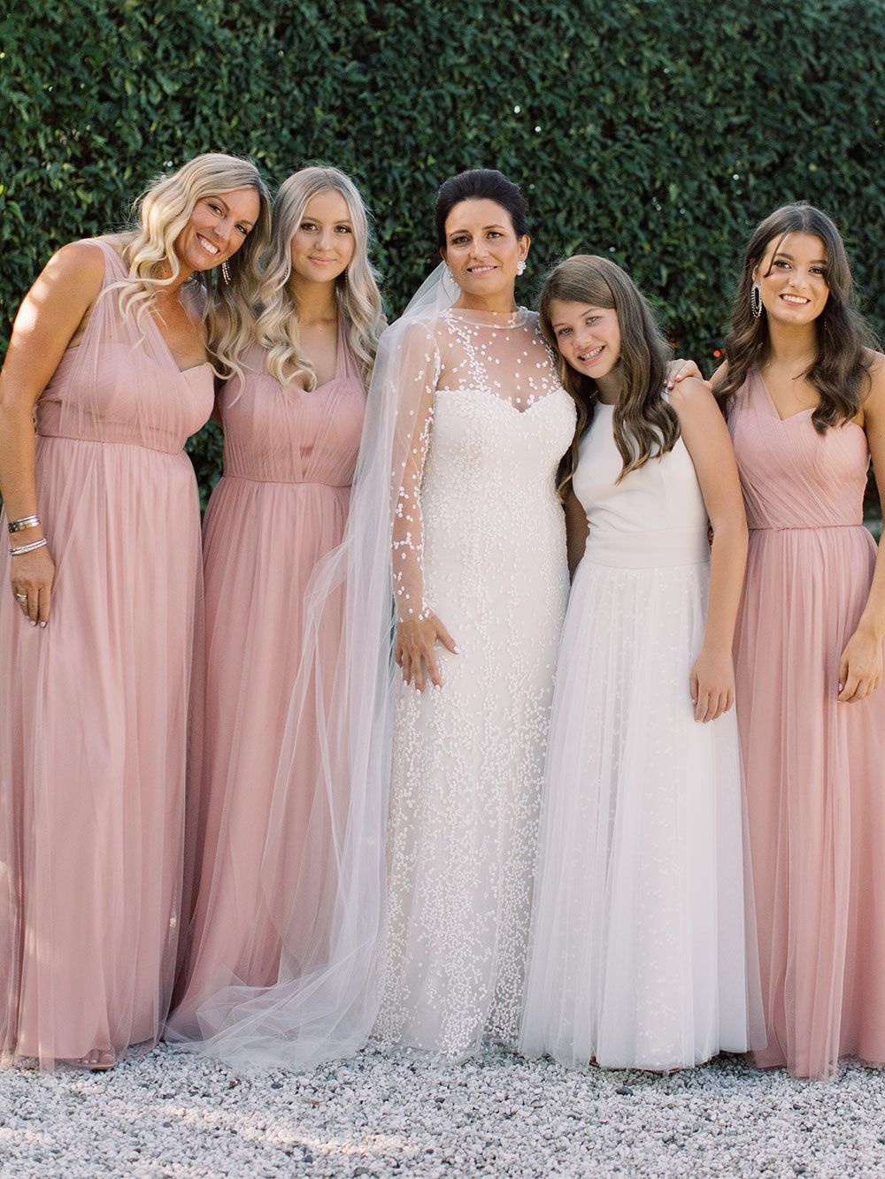 Bride wearing bespoke gown by Auckland wedding dress designer Vinka Design, with a high neckline and delicate spotted embroidery - with bridesmaids near hedge