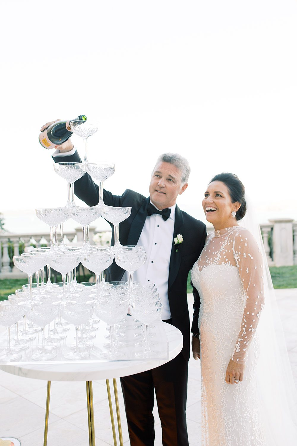 Bride wearing bespoke gown by Auckland wedding dress designer Vinka Design, with a high neckline and delicate spotted embroidery - pouring champagne