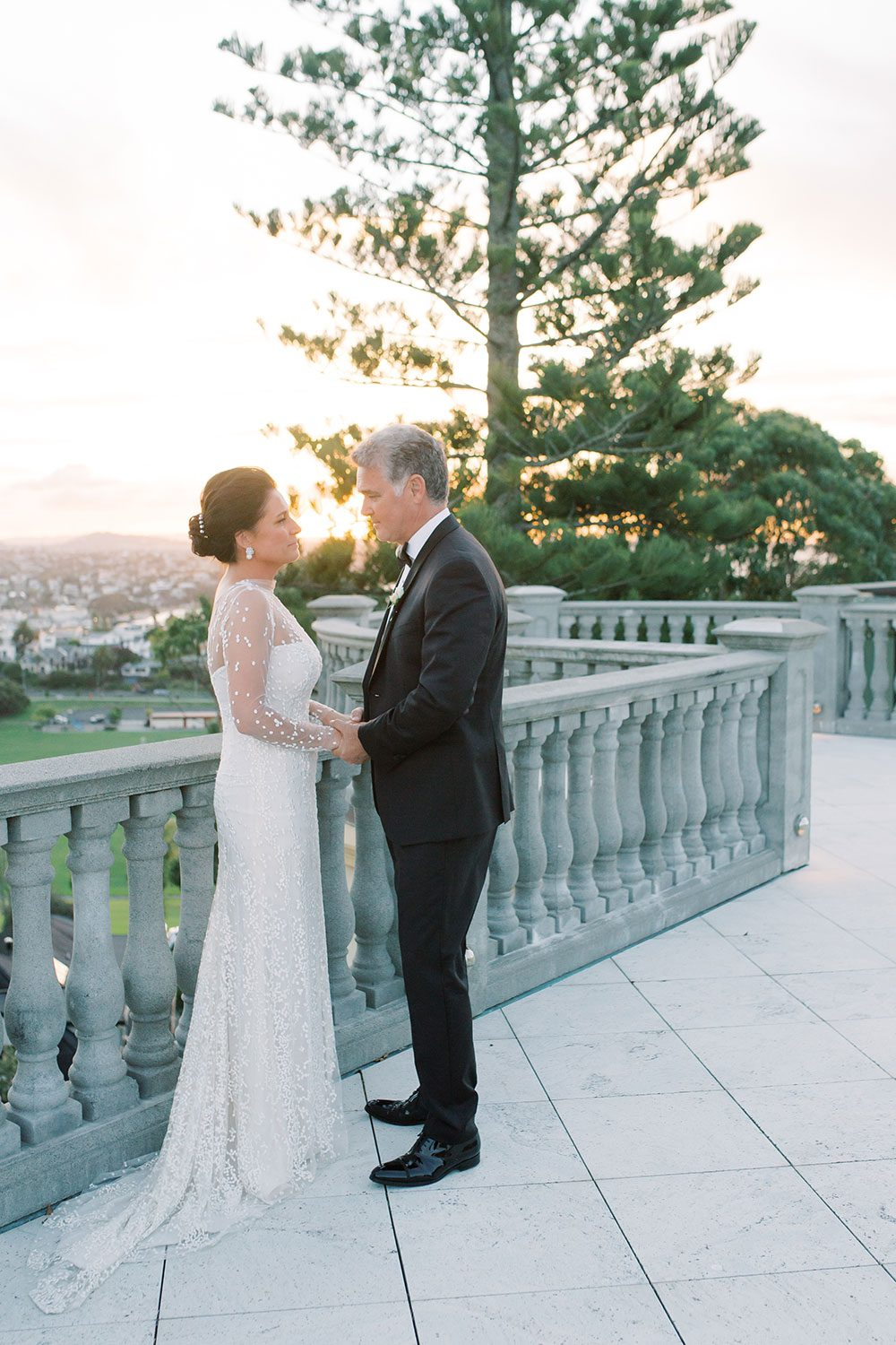 Bride wearing bespoke gown by Auckland wedding dress designer Vinka Design, with a high neckline and delicate spotted embroidery - with groom on balcony