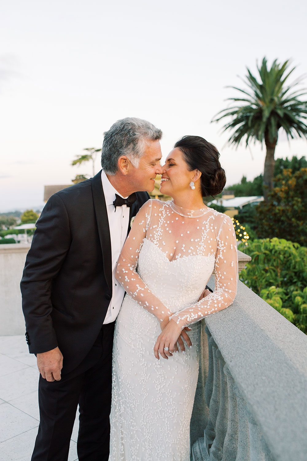 Bride wearing bespoke gown by Auckland wedding dress designer Vinka Design, with a high neckline and delicate spotted embroidery - profile with groom