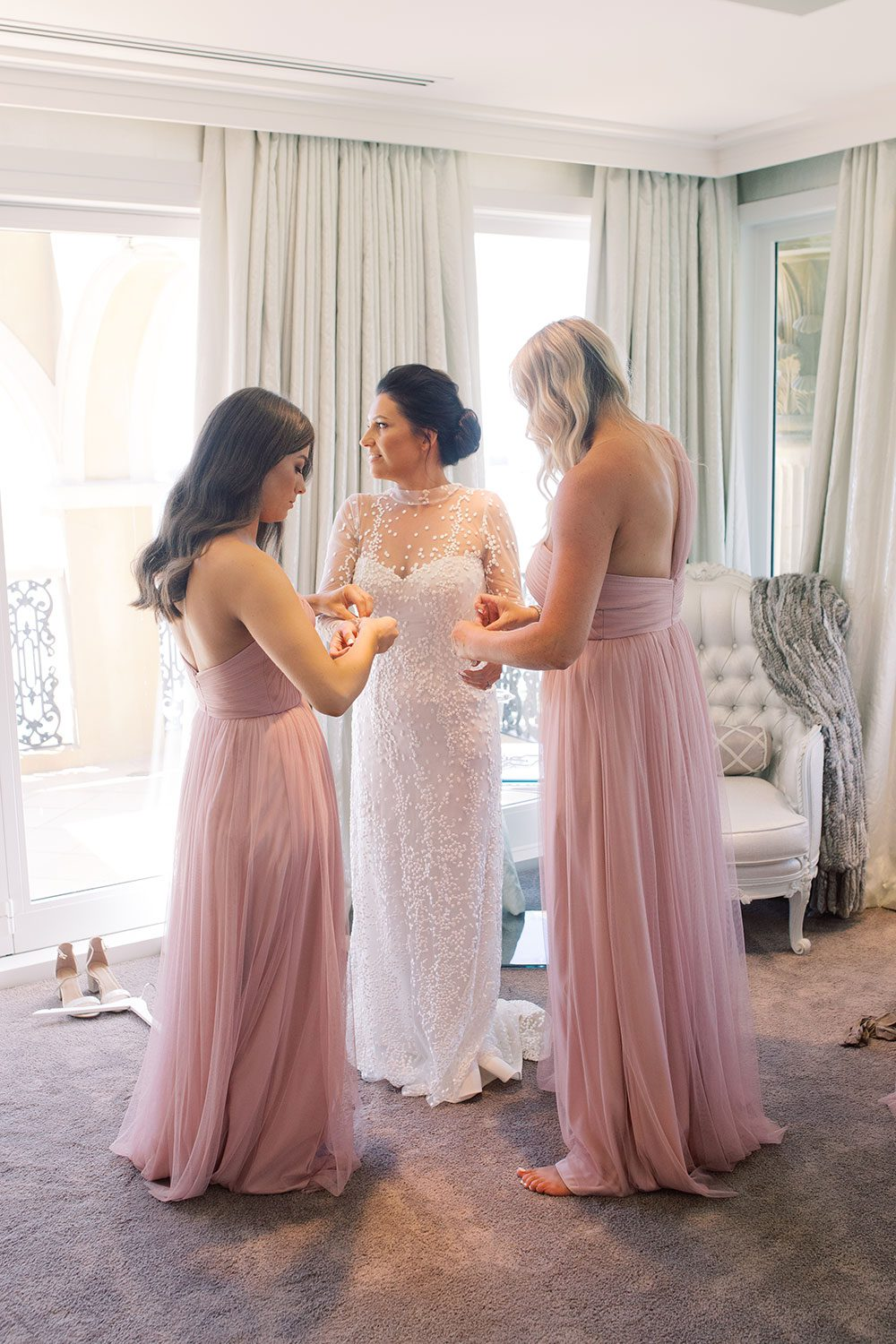 Bride wearing bespoke gown by Auckland wedding dress designer Vinka Design, with a high neckline and delicate spotted embroidery - bride and bridesmaids getting ready