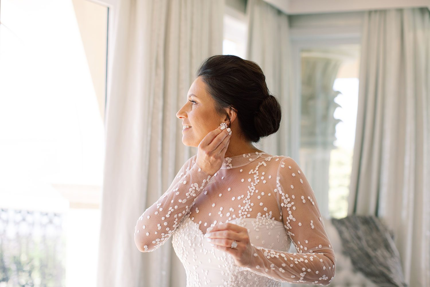 Bride wearing bespoke gown by Auckland wedding dress designer Vinka Design, with a high neckline and delicate spotted embroidery - putting on earrings