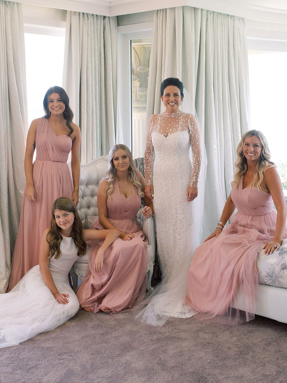 Bride wearing bespoke gown by Auckland wedding dress designer Vinka Design, with a high neckline and delicate spotted embroidery - bride and bridesmaids at window