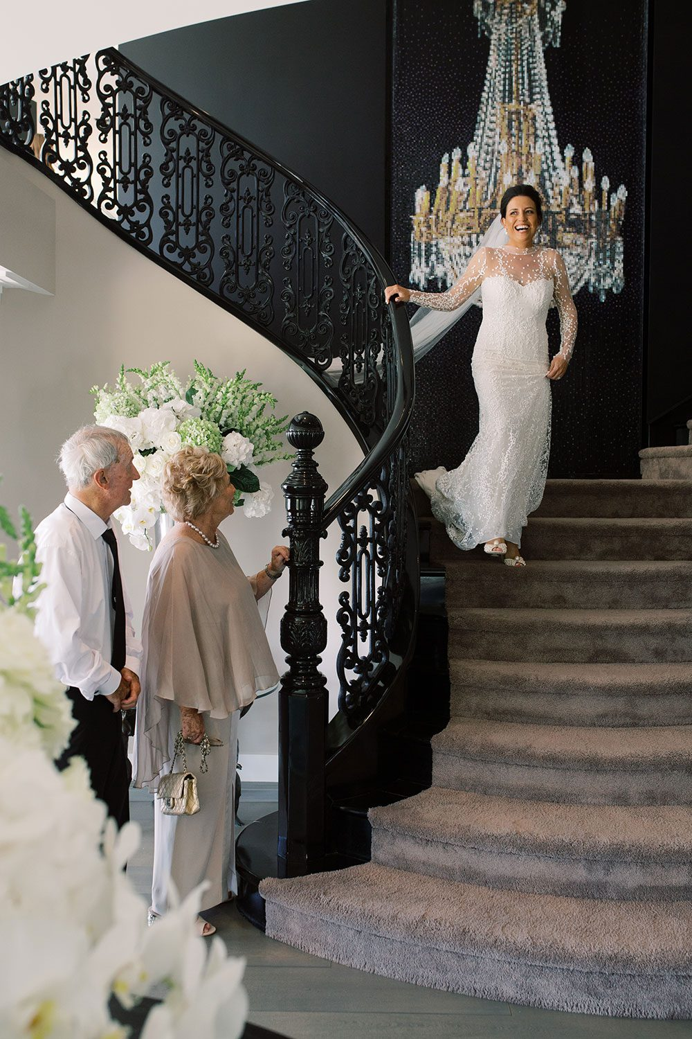 Bride wearing bespoke gown by Auckland wedding dress designer Vinka Design, with a high neckline and delicate spotted embroidery - bride on stairs