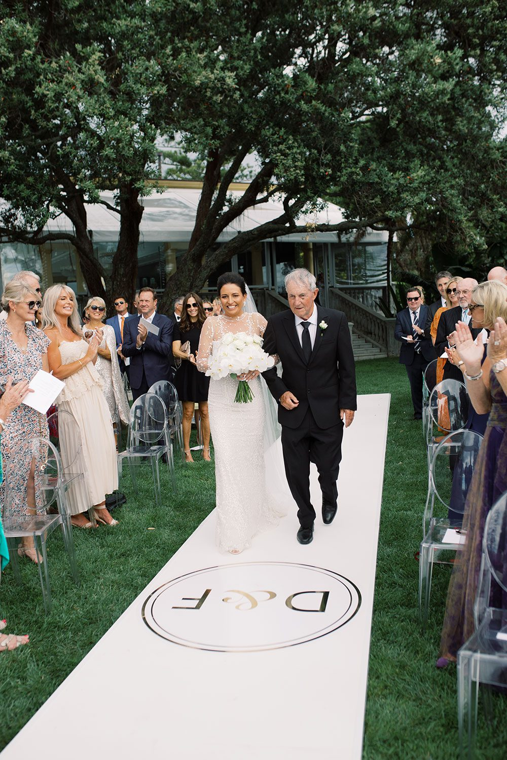 Bride wearing bespoke gown by Auckland wedding dress designer Vinka Design, with a high neckline and delicate spotted embroidery - walking down aisle