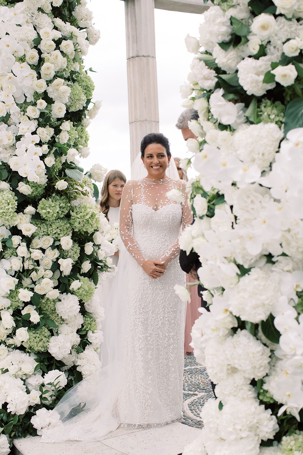 Bride wearing bespoke gown by Auckland wedding dress designer Vinka Design, with a high neckline and delicate spotted embroidery - with flower pillars