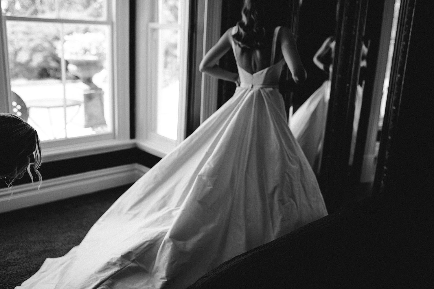 Bride wearing NZ Bespoke Bridal Gown by Vinka Designs, made of silk faile with cowl bodice and detachable overskirt - back view at mirror