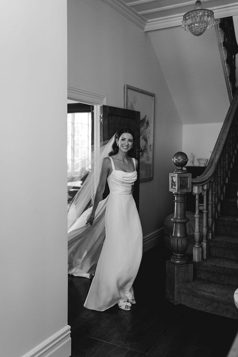 Bride wearing NZ Bespoke Bridal Gown made of silk faile with cowl bodice and detachable overskirt by Vinka Designs - black and white at bottom of stairs