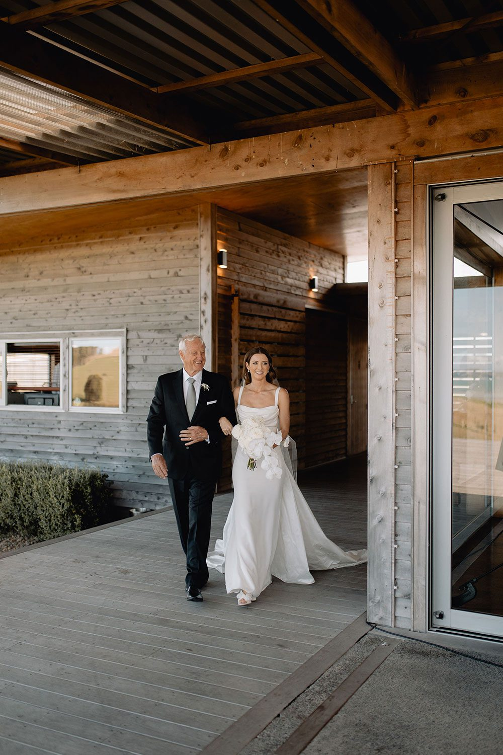 Bride wearing NZ Bespoke Bridal Gown made of silk faile with cowl bodice and detachable overskirt by Vinka Designs - giving away