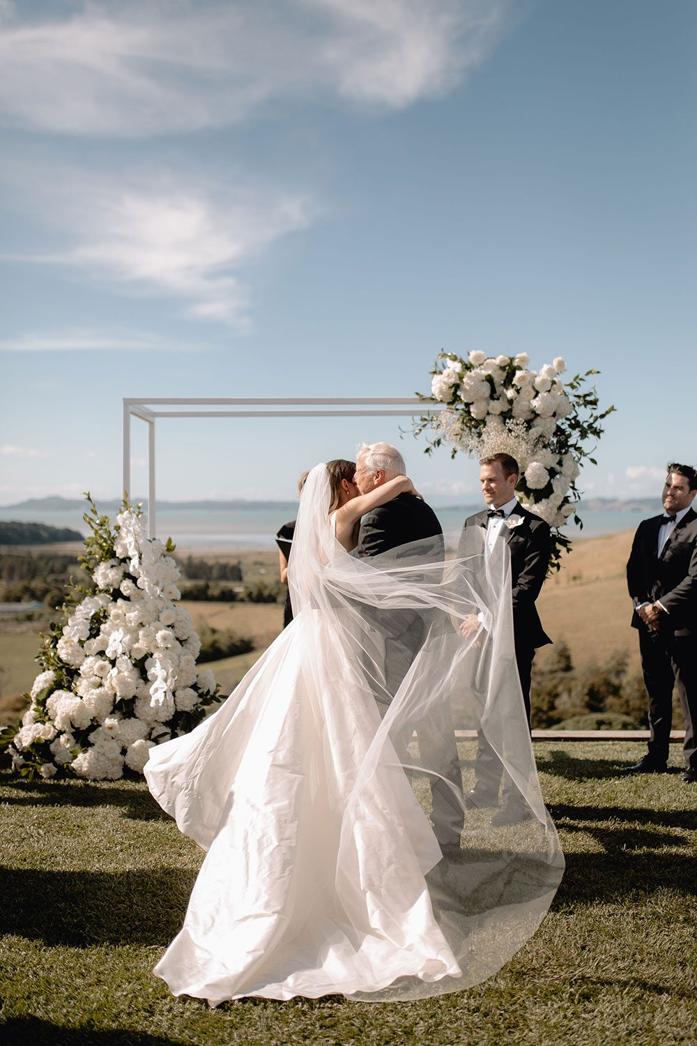 Bride wearing NZ Bespoke Bridal Gown made of silk faile with cowl bodice and detachable overskirt by Vinka Designs - giving away embrace