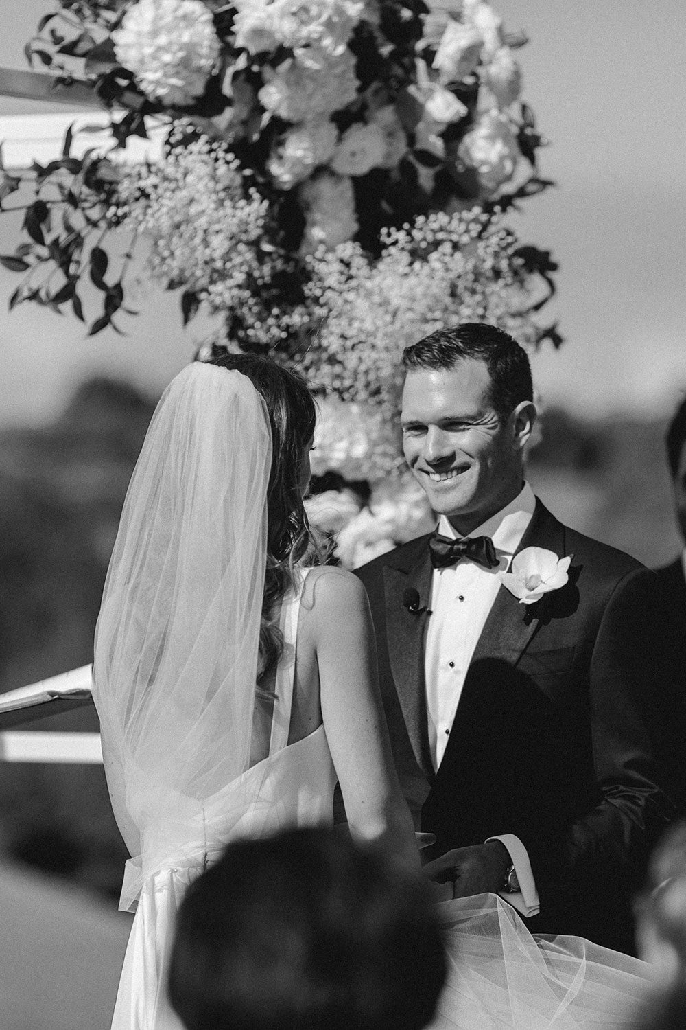 Bride wearing NZ Bespoke Bridal Gown made of silk faile with cowl bodice and detachable overskirt by Vinka Designs - black and white saying vows