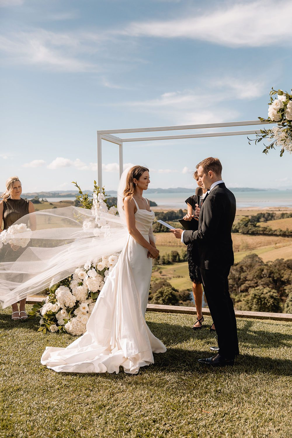 Bride wearing NZ Bespoke Bridal Gown made of silk faile with cowl bodice and detachable overskirt by Vinka Designs - veil in wind at alter