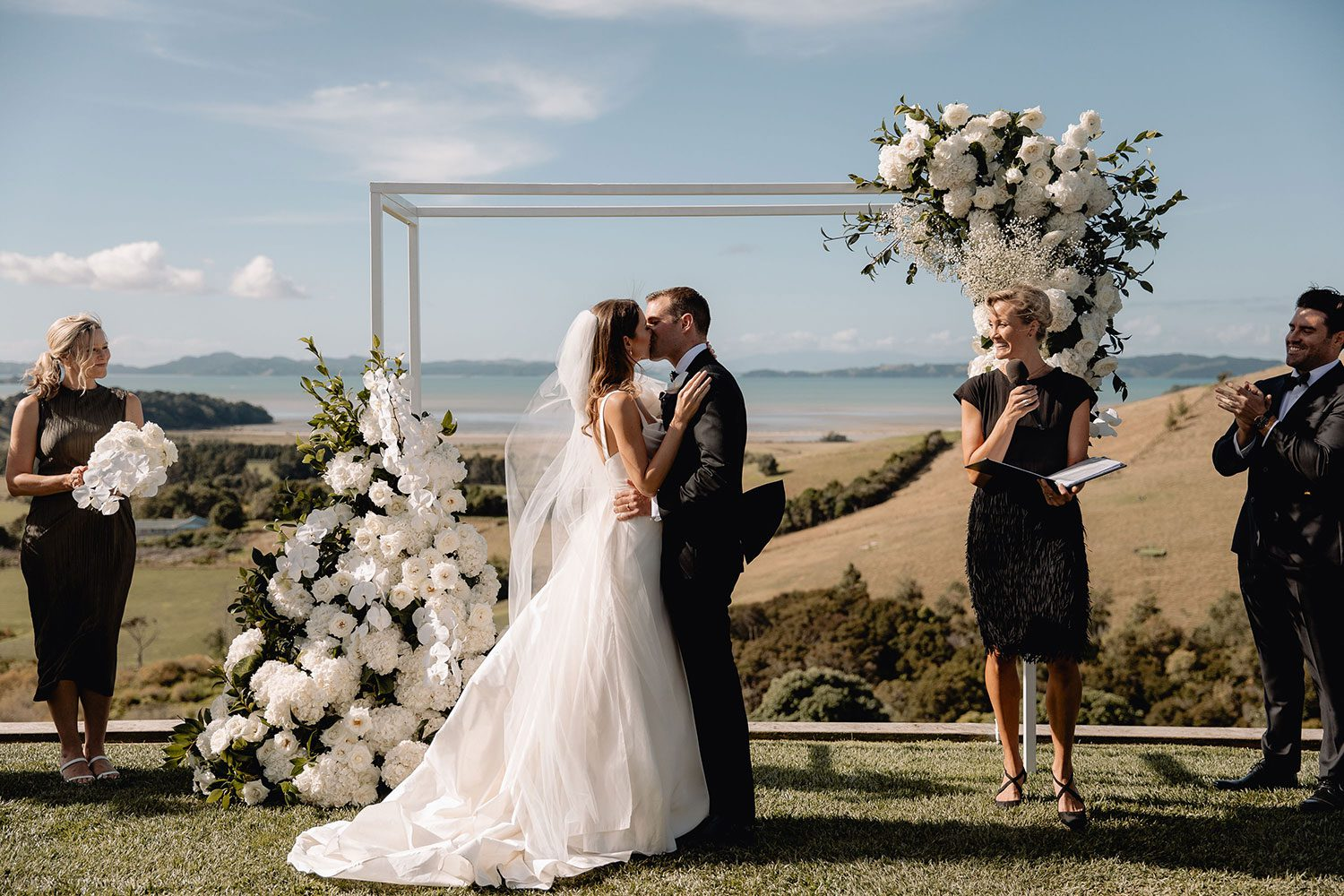 Bride wearing NZ Bespoke Bridal Gown made of silk faile with cowl bodice and detachable overskirt by Vinka Designs - kissing at alter