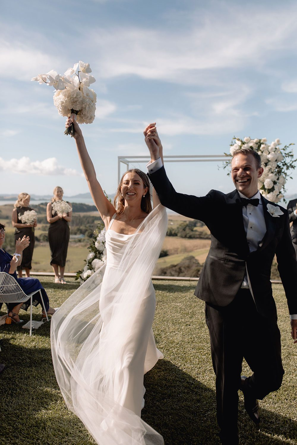 Bride wearing NZ Bespoke Bridal Gown made of silk faile with cowl bodice and detachable overskirt by Vinka Designs - just married