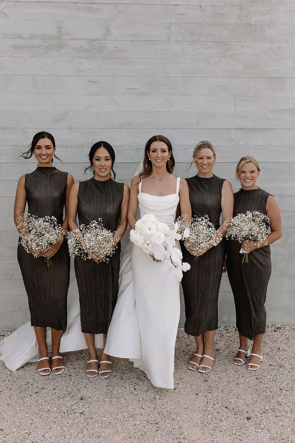 Bride wearing NZ Bespoke Bridal Gown made of silk faile with cowl bodice and detachable overskirt by Vinka Designs - with bridesmaids and bouquets