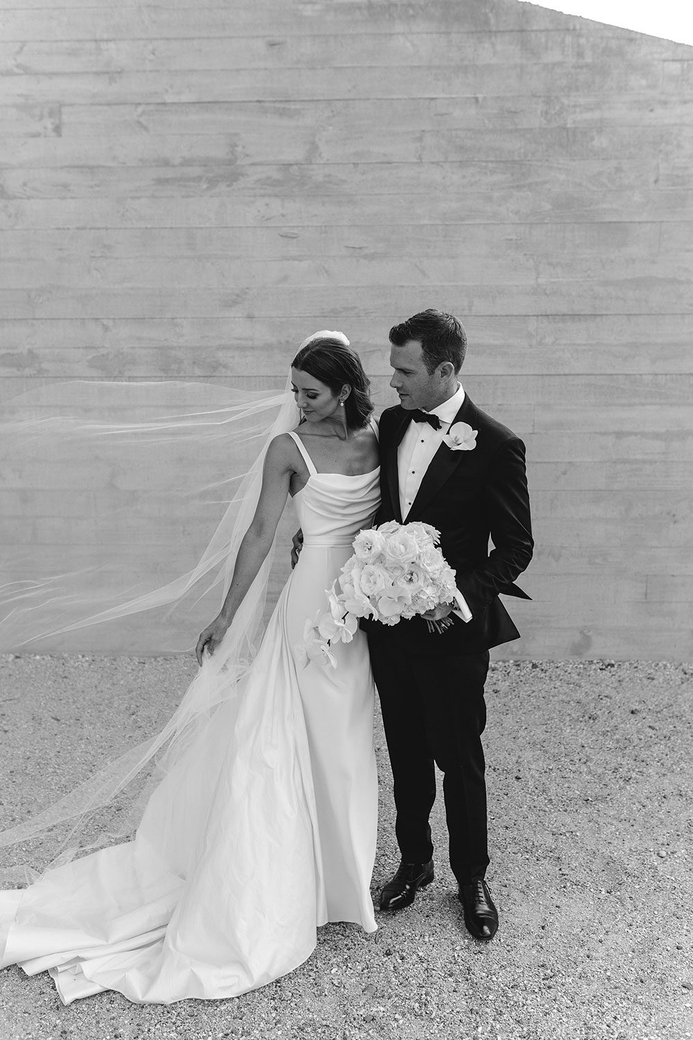 Bride wearing NZ Bespoke Bridal Gown made of silk faile with cowl bodice and detachable overskirt by Vinka Designs - black and white looking to side with groom