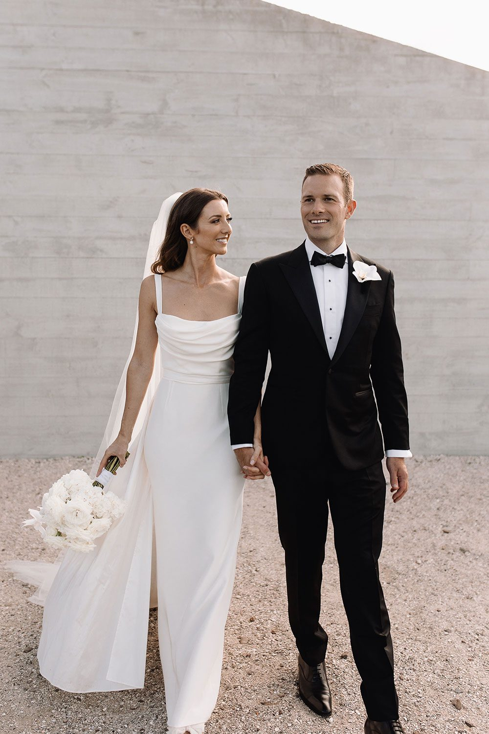 Bride wearing NZ Bespoke Bridal Gown made of silk faile with cowl bodice and detachable overskirt by Vinka Designs - in front of wall walking with groom