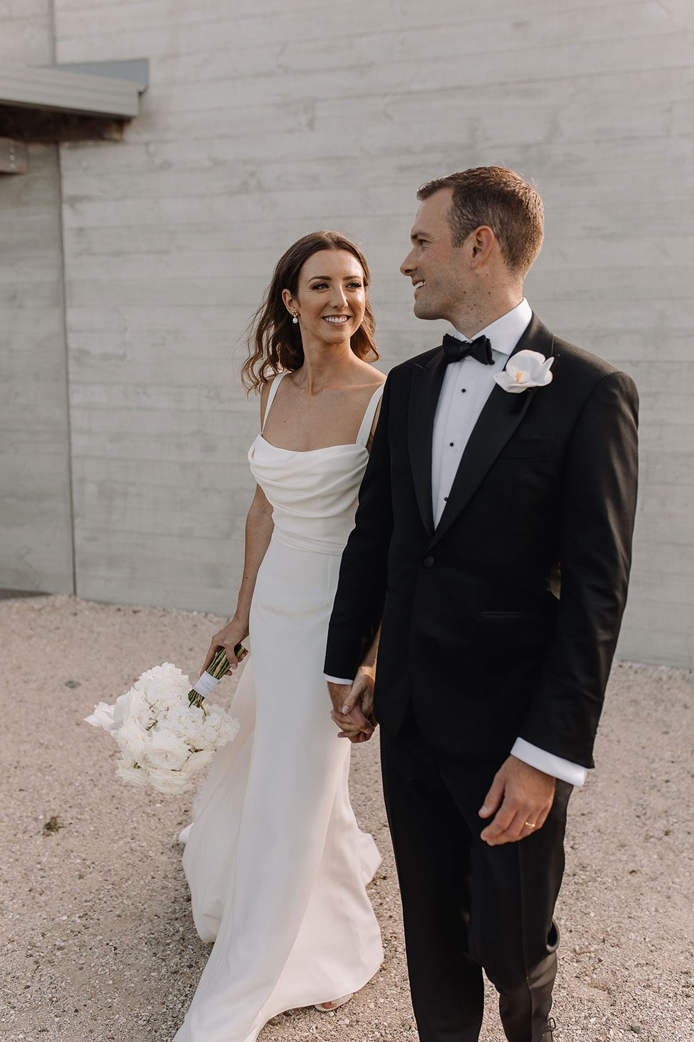 Bride wearing NZ Bespoke Bridal Gown made of silk faile with cowl bodice and detachable overskirt by Vinka Designs - in front of wall smiling at groom