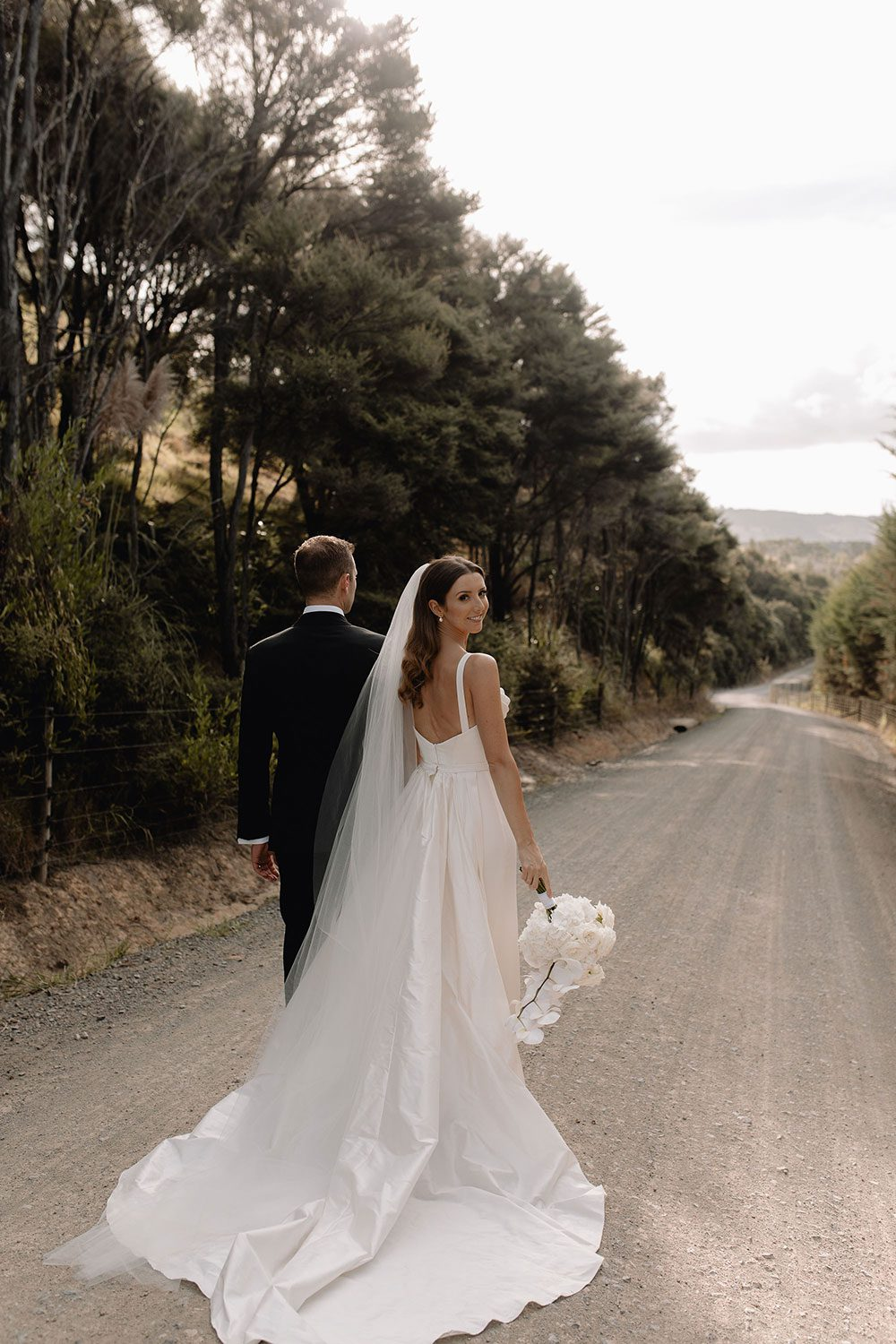 Bride wearing NZ Bespoke Bridal Gown made of silk faile with cowl bodice and detachable overskirt by Vinka Designs - looking back with groom on road