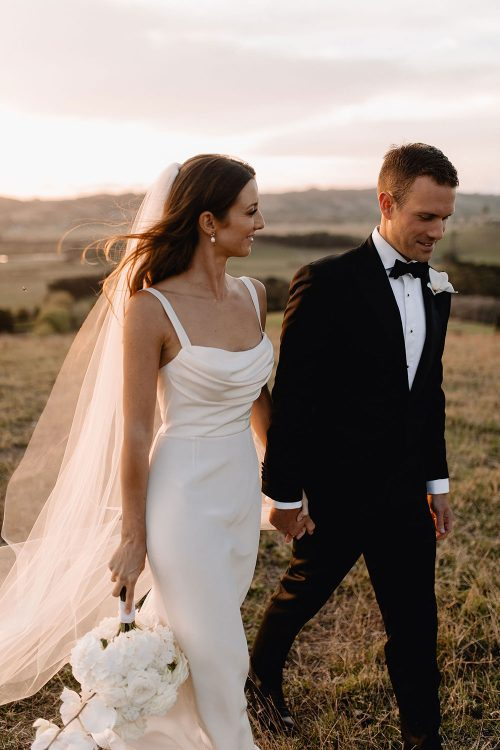 Bride wearing NZ Bespoke Bridal Gown Bride wearing NZ Bespoke Bridal Gown made of silk faile with cowl bodice and detachable overskirt by Vinka Designs - looking back with groom on road by Vinka Designs - on field with groom