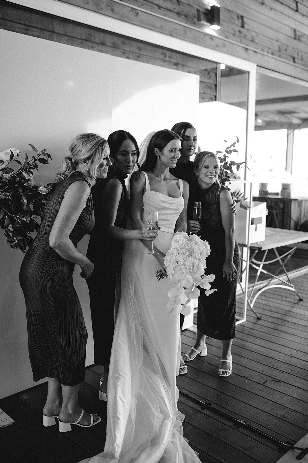 Bride wearing NZ Bespoke Bridal Gown made of silk faile with cowl bodice and detachable overskirt by Vinka Designs - black and white with bridesmaids
