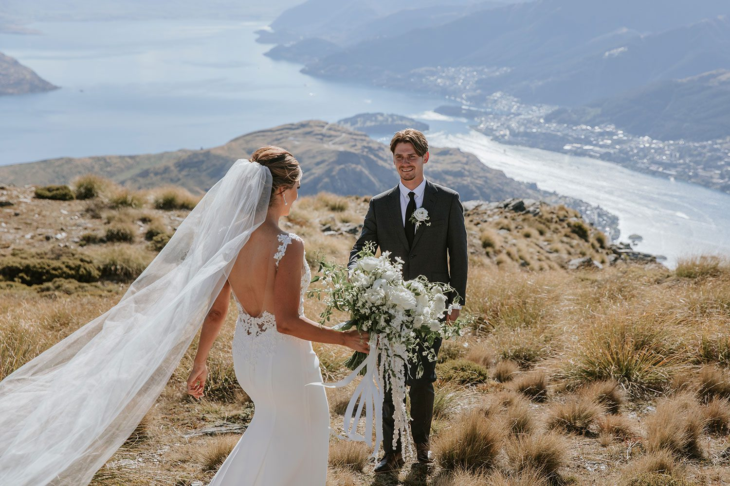 Bride wearing bespoke bridal gown with richly beaded lace over sheer tulle bodice and low back from Auckland wedding dress maker Vinka designs - meeting groom on hill