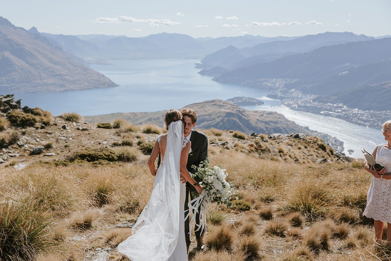 Bride wearing bespoke bridal gown with richly beaded lace over sheer tulle bodice and low back from Auckland wedding dress designer Vinka designs - meeting groom on hill long shot