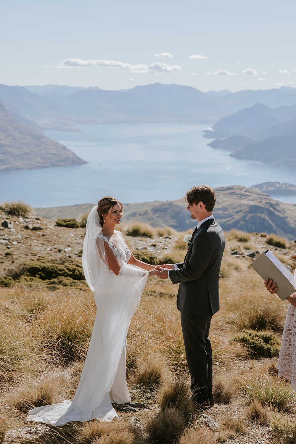 Bride wearing bespoke bridal gown with richly beaded lace over sheer tulle bodice and low back from Auckland wedding dress designer Vinka designs - saying vows view of lake