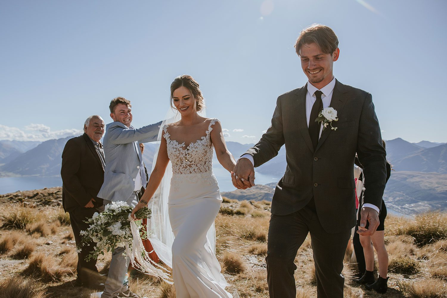 Bride wearing bespoke bridal gown with richly beaded lace over sheer tulle bodice and low back from Auckland wedding dress designer Vinka designs - just married walking out