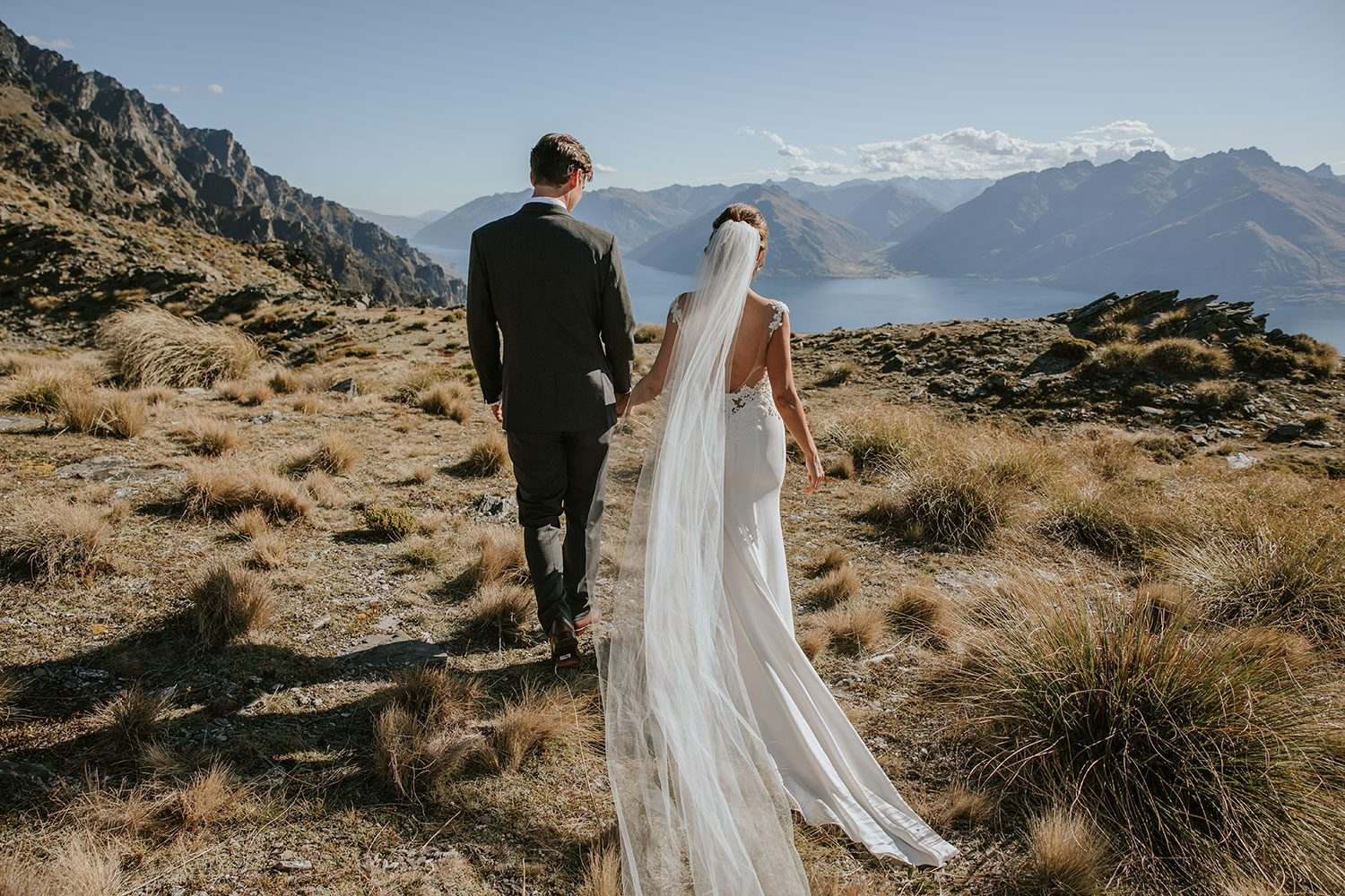 Bride wearing bespoke bridal gown with richly beaded lace over sheer tulle bodice and low back from Auckland wedding dress designer Vinka designs -hand in hand walking away