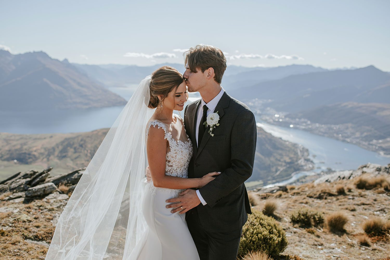 Bride wearing bespoke bridal gown with richly beaded lace over sheer tulle bodice and low back from Auckland wedding dress designer Vinka designs -profile with groom on hill
