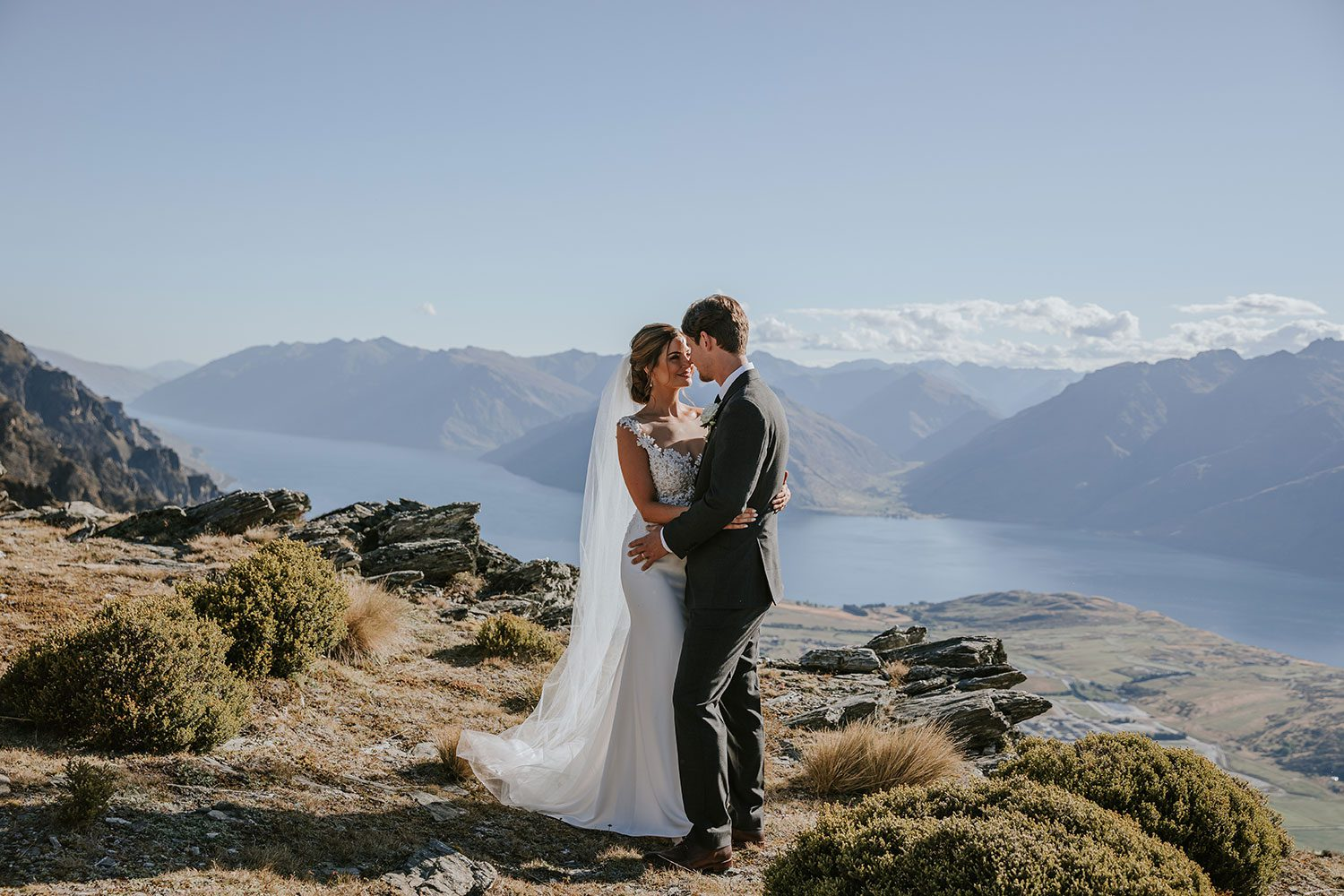 Bride wearing bespoke bridal gown with richly beaded lace over sheer tulle bodice and low back from Auckland wedding dress designer Vinka designs - embrace with groom on hill