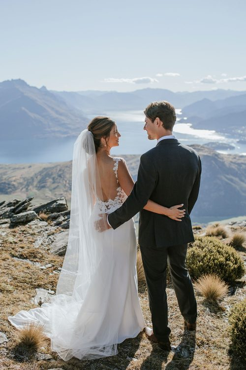 Bride wearing bespoke bridal gown with richly beaded lace over sheer tulle bodice and low back from Auckland wedding dress designer Vinka designs - back embrace with groom
